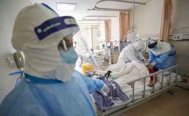 Medical workers in protective suits attend to a patient inside an isolated ward of Wuhan Red Cross Hospital in Wuhan, the epicentre of the novel coronavirus outbreak