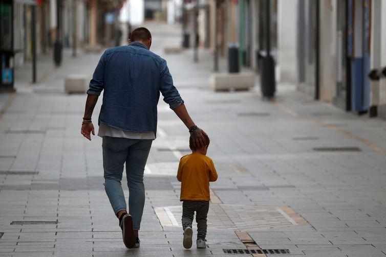 Pai e filho caminham juntos em meio a pandemia de covid-19 na Espanha.