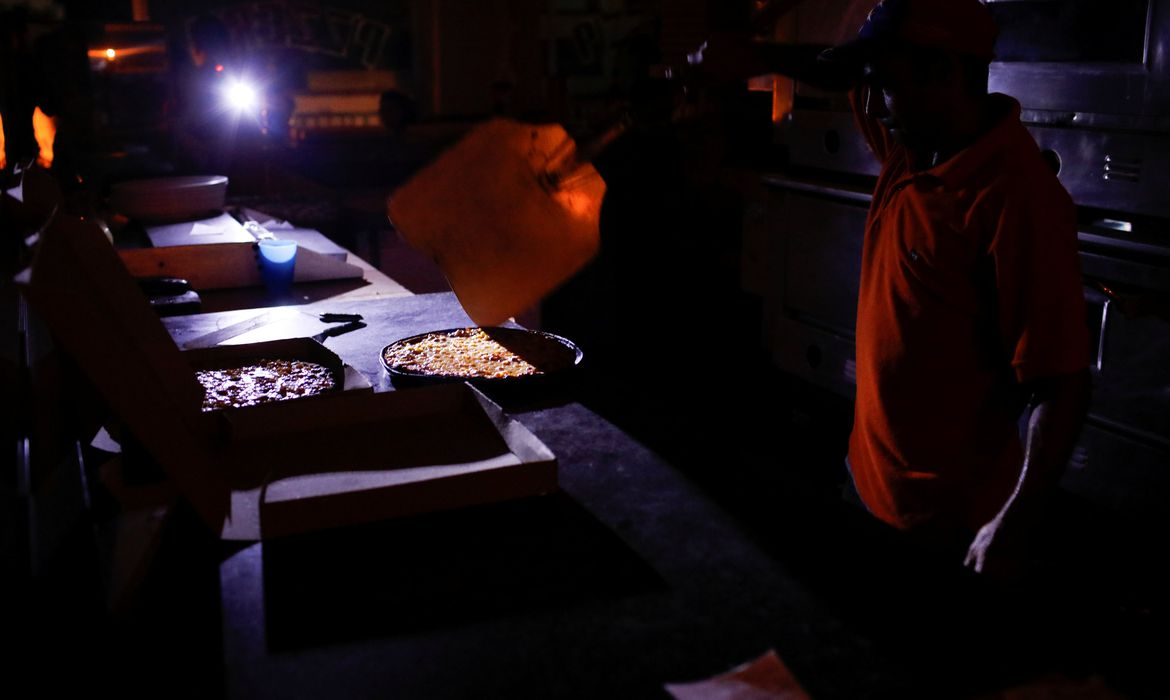 A man cooks with candlelight and lanterns at a pizzeria during a second day of blackout in Caracas, Venezuela March 9, 2019. REUTERS/Marco Bello