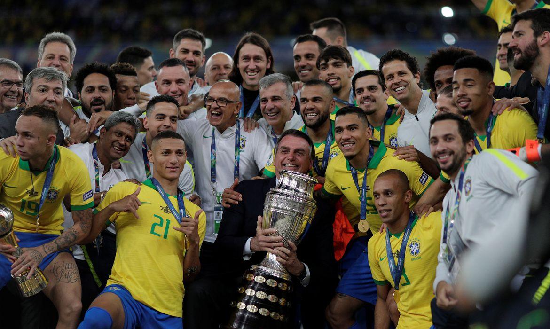 Soccer Football - Copa America Brazil 2019 - Final - Brazil v Peru - Maracana Stadium, Rio de Janeiro, Brazil - July 7, 2019    Brazil's President Jair Bolsonaro and the players celebrate winning the Copa America with the trophy      REUTERS