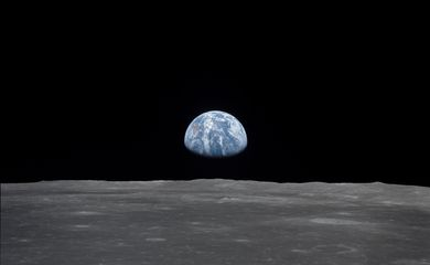 View of Moon limb with Earth on the horizon,Mare Smythii Region. Earth rise. This image was taken before separation of the LM and the Command Module during Apollo 11 Mission. Original film magazine was labeled V. Film Type: S0-368 Color taken