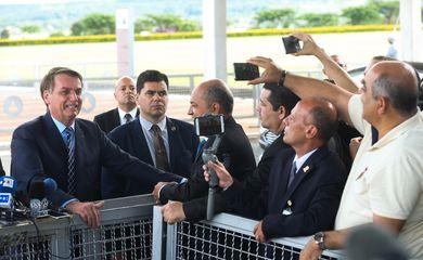 O presidente Jair Bolsonaro fala à imprensa e cumprimenta populares ao sair do Palácio da Alvorada