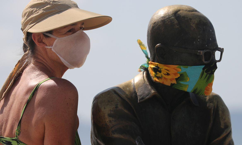 Uma mulher posa para uma foto ao lado da estátua do escritor brasileiro Carlos Drummond de Andrade que usa uma máscara protetora no primeiro dia de uso obrigatório de máscaras  em meio ao surto de doença por coronavírus (COVID-19), na praia de Copacabana