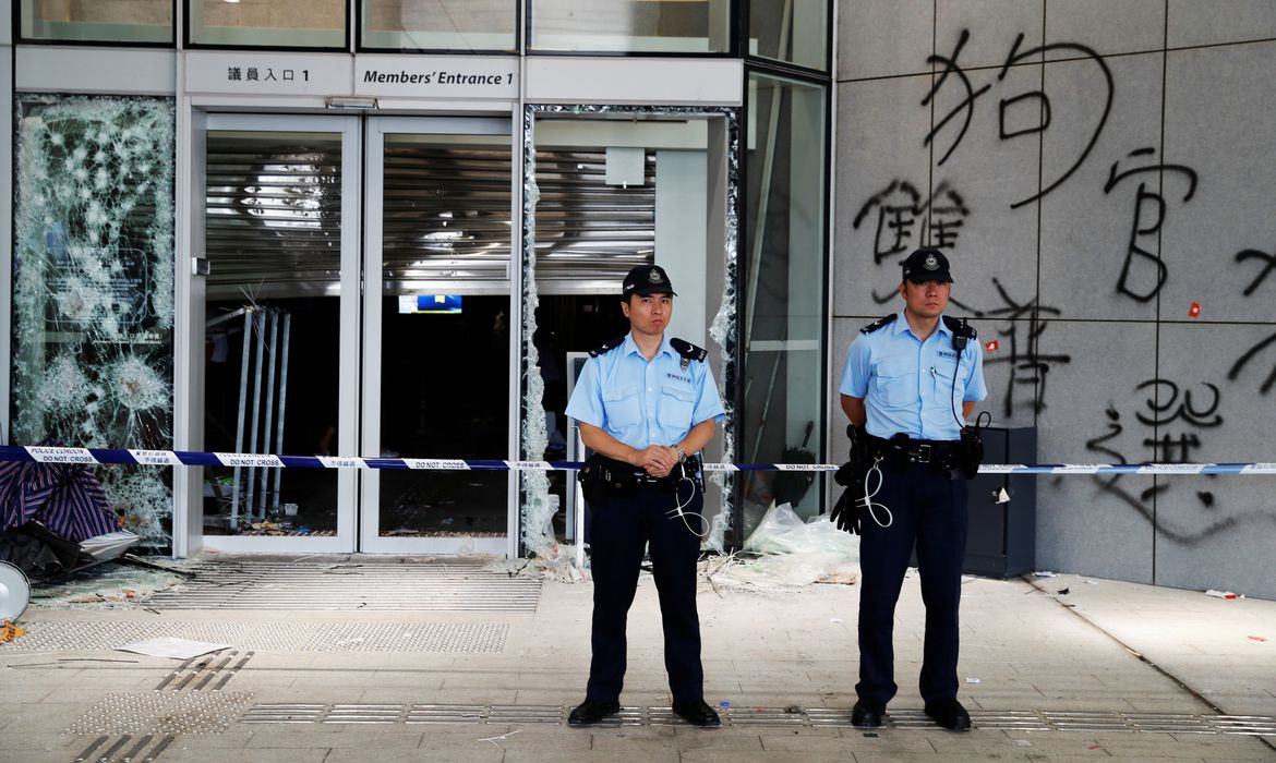 Policemen stand in front of graffiti on the walls of the Legislative Council, a day after protesters broke into the building in Hong Kong, China July 2, 2019.  REUTERS/Jorge Silva