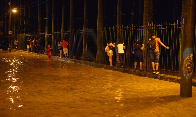 Moradores caminham segurando uma cerca ao lado de uma rua alagada durante fortes chuvas no bairro Jardim Botânico