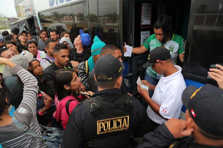 Imigrantes venezuelanos apresentam documentos ao subirem em ônibus que os levará a Trujillo, no Peru