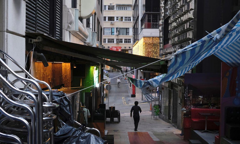 Homem caminha perto de pub fechado por causa da Covid-19 em Hong Kong