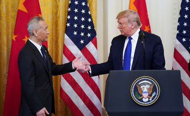 Chinese Vice Premier Liu He reaches out to U.S. President Donald Trump as he approaches the podium to speak during a signing ceremony for