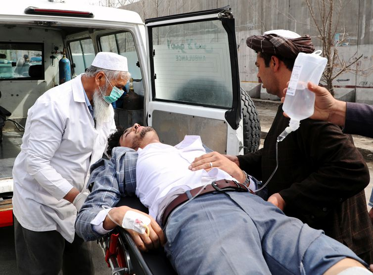 Hospital workers carry an injured person after an attack in Kabul