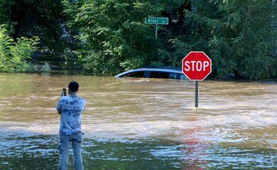 A man takes photos of a submerged car in Passaic