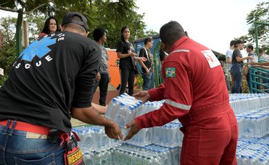 REFILE - CORRECTING GRAMMR Volunteers pass bottles of water for people affected by a failed iron ore tailings dam owned by Brazilian miner Vale SA that burst, in Brumadinho, Brazil January 27, 2019. REUTERS/Washington Alves