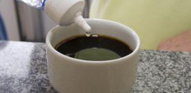 Pessoa pinga uma gota de adoçante em xícara de café