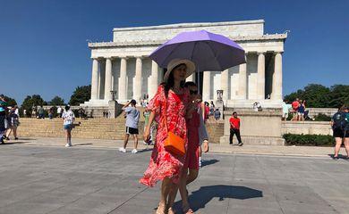 Turista se protege do sol usando um guarda-chuva em frente ao Lincoln Memorial, em dia de forte calor em Washington, EUA.