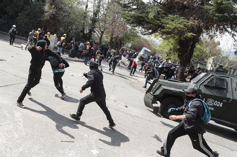 Manifestantes encapuzados enfrentam a polícia chilena durante manifestação que lembrou os 45 anos do golpe militar no país