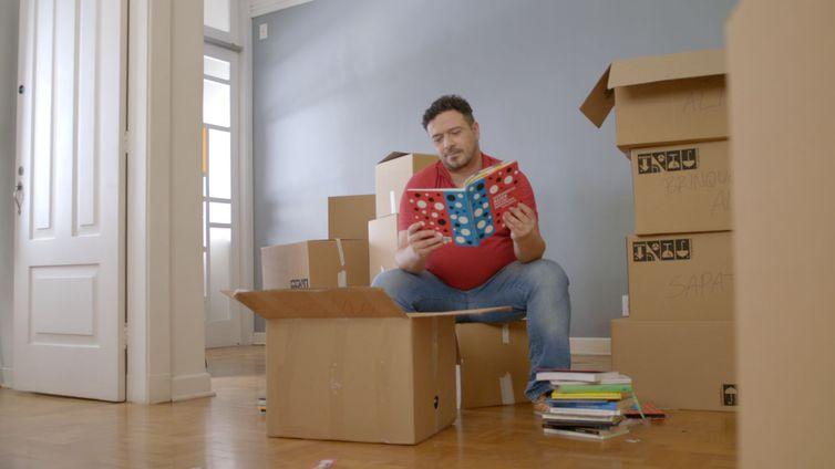 Alberto empacota seus objetos para mudança