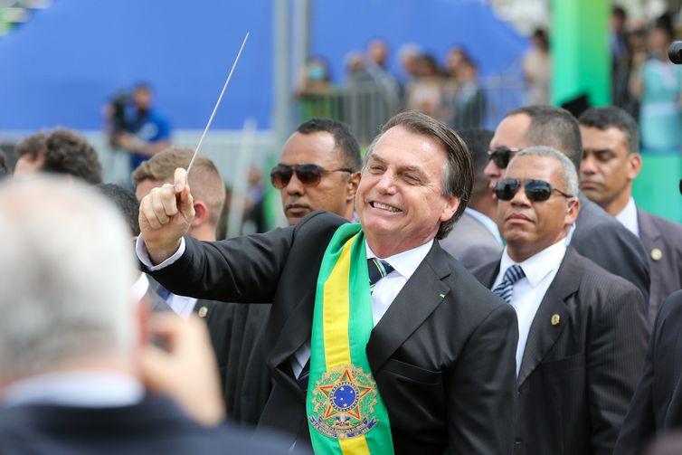 O presidente Jair Bolsonaro,quebra o protocolo  desce do palanque, pega uma batuta e faz gestos de maestro ao se aproximar a pé, das arquibancadas onde fica o público na Esplanada dos Ministérios