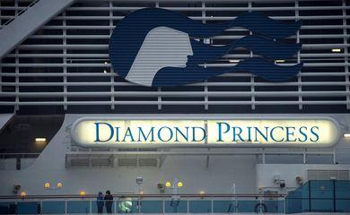 Os passageiros que usam máscaras protetoras são vistos no navio de cruzeiro Diamond Princess, enquanto os passageiros da embarcação continuam sendo testados quanto a coronavírus, no terminal de cruzeiros do cais de Daikoku, em Yokohama.