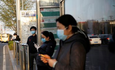 People wearing face masks wait for buses at a bus stop, as the country is hit by an outbreak of the novel coronavirus disease (COVID-19), in Beijing