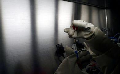 Um cientista da Agência de Ciência e Tecnologia da Equipe Doméstica (HTX) demonstra, sem uma amostra viva, o processo de extração do kit de teste de coronavírus em seu laboratório em Cingapura, em 5 de março de 2020. Esses kits de teste, uma