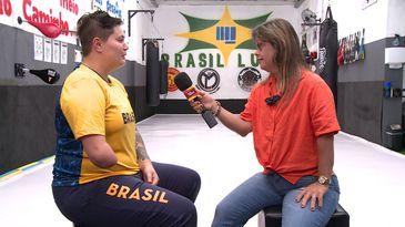 Academia de luta. Sentadas frente a frente, Débora e Fernanda, com o microfone do Programa Especial, na mão direita, apontado para a atleta. Ao fundo, sacos de boxe pendurados nas paredes