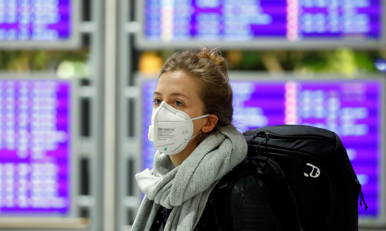 Flight passenger wears a protective mask at Frankfurt Airport