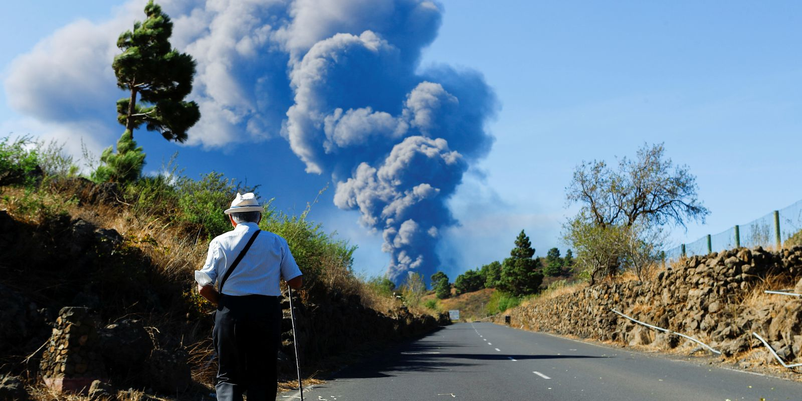 A man walks along an El Paso road while observing a large ash column from the Cumbre Vieja volcano on the Canary Island of La Palma