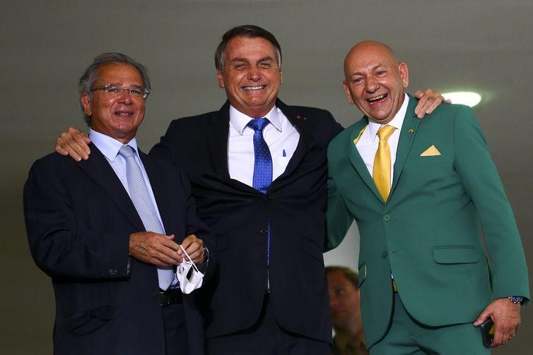 O empresário Luciano Hang, o presidente Jair Bolsonaro e o ministro da Economia, Paulo Guedes, durante o lançamento do programa Voo Simples, no Palácio do Planalto.