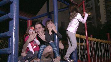 Adriano Bisker, cercado por duas filhas crianças, posa para foto em um trepa trepa, a terceira filha, mais velha, está mais atrás