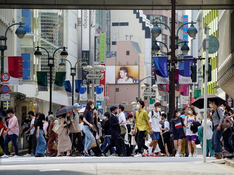 Pedestres usam máscaras de proteção enquanto caminham sob rua decorada para os Jogos Olímpicos e Paralímpicos da Tóquio-2020 no Japão - anéis - transeuntes - Olimpíada