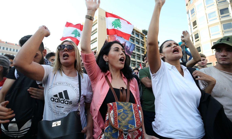 Manifestantes carregam bandeiras nacionais durante um protesto contra o governo no centro de Beirute, Líbano, em 20 de outubro de 2019