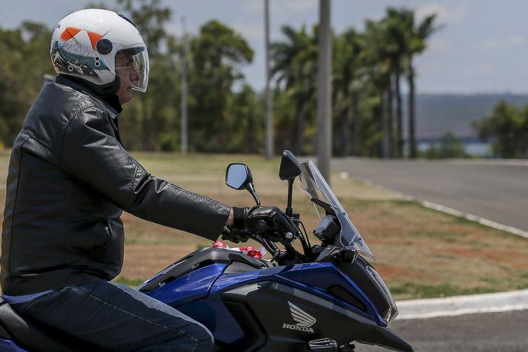 O presidente Jair Bolsonaro chega de moto ao Palácio da Alvorada e cumprimenta turistas