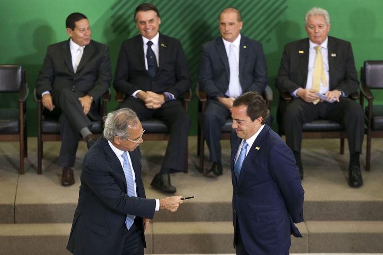 O ministro da Economia Paulo Guedes, assina o termo de posse do presidente da Caixa, Pedro Guimarães, durante cerimônia de posse aos presidentes dos bancos públicos.