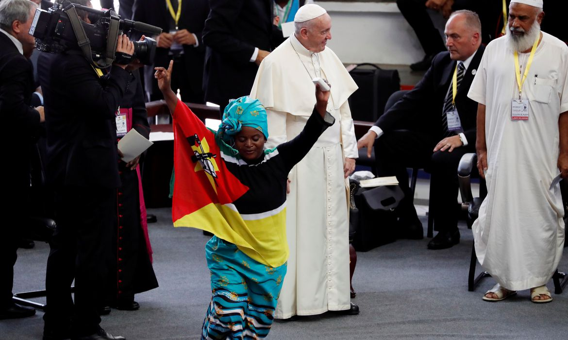 Faithful dances as Pope Francis is seen at the background during an interreligious meeting at Maxaquene Pavilion in Maputo, Mozambique September 5, 2019. REUTERS/Yara Nardi