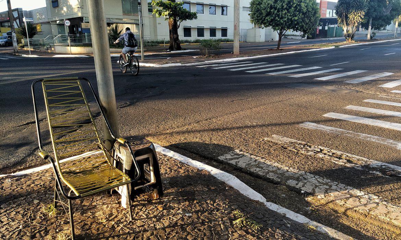 Rua remota durante a pandemia.  No primeiro plano da foto, cadeira de balanço e faixas de pedestre. Ao fundo, ciclista solitário em uma rua vazia.
