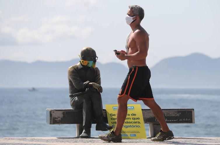 Um homem caminha ao lado da estátua do escritor brasileiro Carlos Drummond de Andrade que usa máscara protetora no primeiro dia de uso obrigatório de máscaras  em meio ao surto de doença por coronavírus (COVID-19), na praia de Copacabana