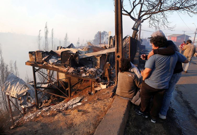 People react next to the debris of their house following the spread of wildfires in Valparaiso, Chile, December 24, 2019. REUTERS/Rodrigo Garrido
