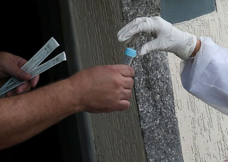 m homem recebe um teste de auto-coronavírus de um estudante de medicina à sua porta, em meio ao surto de doença de coronavírus (COVID-19), em São Caetano do Sul, São Paulo, Brasil, 14 de abril de 2020. REUTERS / Rahel Patrasso