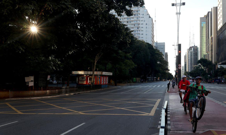 A Avenida Paulista é vista vazia enquanto os entregadores andam de bicicleta no primeiro dia de um bloqueio imposto pelo governo estadual por causa do surto de doença por coronavírus (COVID-19)