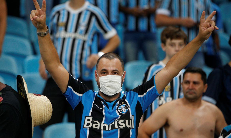 Torcedor com máscara contra coronavírus no jogo entre Grêmio e Internacional