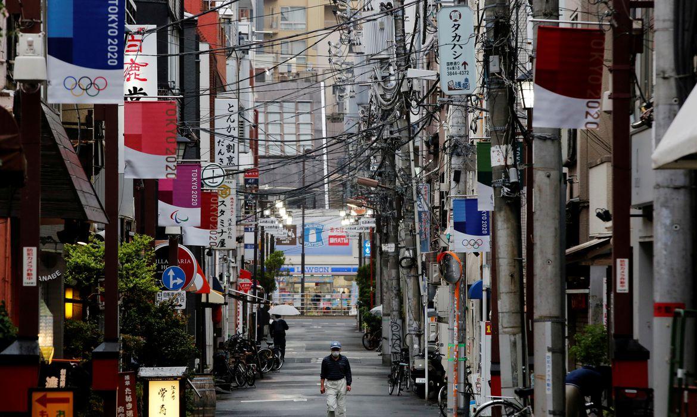 Homem com máscara de proteção caminha em rua comercial decorada com bandeiras da Olimpíada Tóquio 2020 em Tóquio - anéis - rua