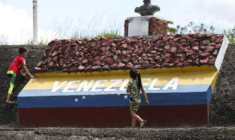 Crianças brincam em marco da fronteira entre Brasil e Venezuela.