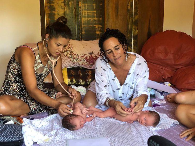 As parteiras Mayra Calvete (esquerda) e Naoli Vinaver (direita) fazem checagem em bebês após o parto