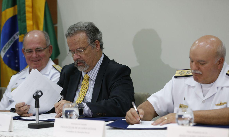 O ministro da Segurança Pública, Raul Jungmann, e o comandante de operações navais, Almirnte Küster, ao lado do comandante da Marinha, Almirante Leal Ferreira, assinam acordo de cooperação para ampliar o sistema de monitoramento e controle de