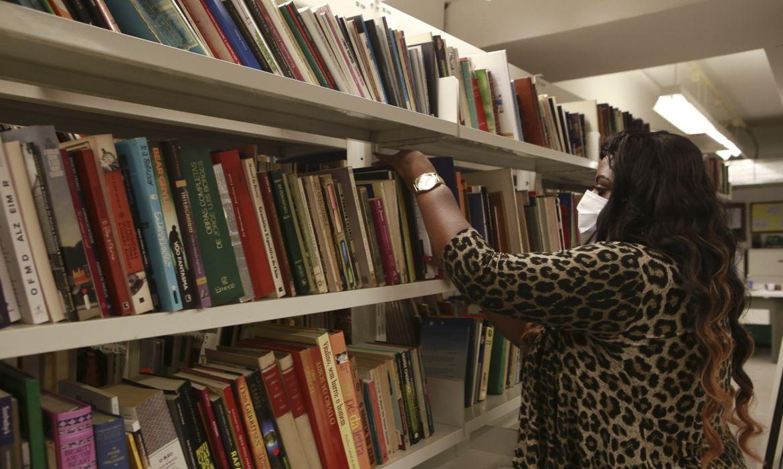 Claudete Costa, assessora do Superintendente de Leitura, examina livros doados através do projeto Rota da Leitura.