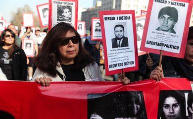 Manifestantes marcharam com cartazes que estampavam rostos de desaparecidos políticos durante a ditadura de Augusto Pinochet