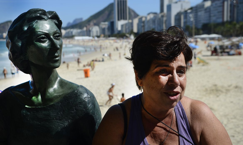 Rio de Janeiro - A educadora ambiental Elisabeth Carvalho emociona-se ao lado da estátua da escritora Clarice Lispector, no Leme (Fernando Frazão/Agência Brasil)
