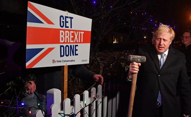 Britain's Prime Minister and Conservative party leader Boris Johnson poses with a sledgehammer, after hammering a